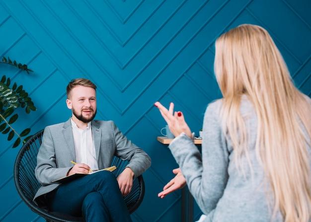 Blonde jeune femme assise devant son psychologue discutant de ses problèmes