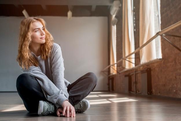 Blonde jeune femme assise sur un plancher de bois franc dans le studio de danse