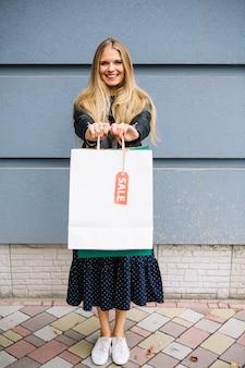 Blonde jeune femme debout contre le mur montrant des sacs à provisions avec étiquette de vente