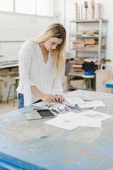 Blonde jeune femme dessinant sur du papier blanc en atelier