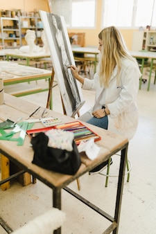 Blonde jeune femme dessinant sur toile en atelier