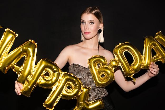 Blonde jeune femme élégante tenant des ballons en forme de lettre de couleur dorée tout en ayant une fête d'anniversaire ou en félicitant quelqu'un