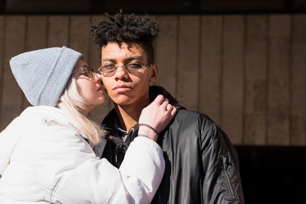 Blonde jeune femme embrasse son copain sur sa joue