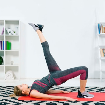 Blonde jeune femme faisant des exercices de détente à la maison