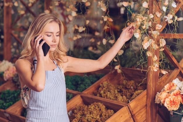 Blonde jeune femme fleuriste parle au téléphone portable