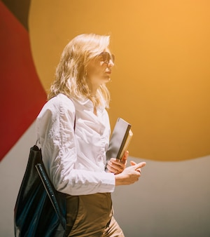 Blonde jeune femme marchant avec des journaux intimes à la main