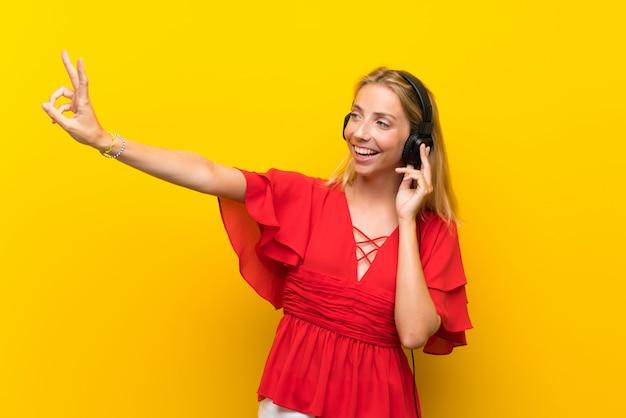 Blonde jeune femme sur un mur jaune isolé, écouter de la musique avec des écouteurs