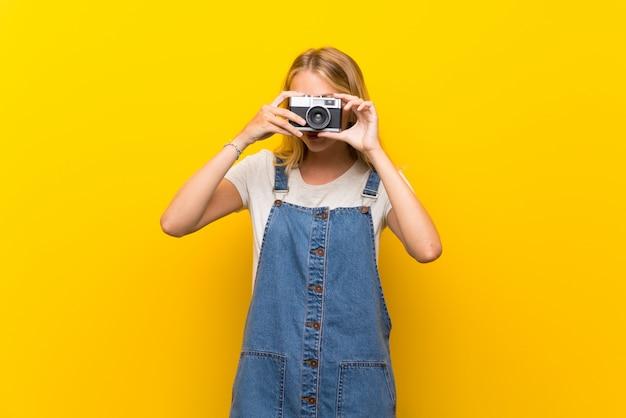 Blonde jeune femme sur un mur jaune isolé, tenant une caméra