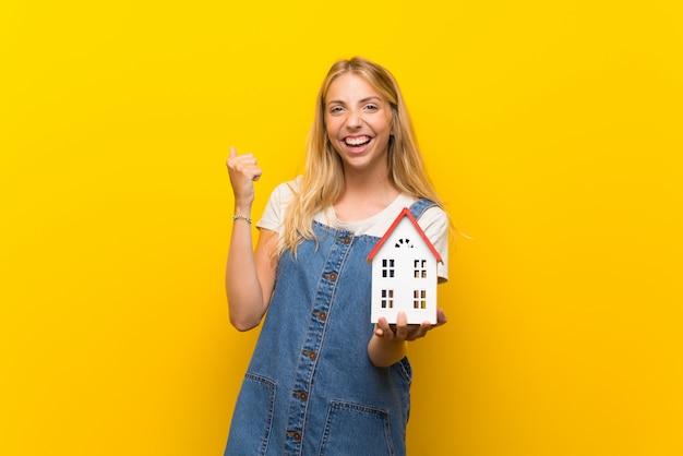 Blonde jeune femme sur un mur jaune isolé tenant une petite maison