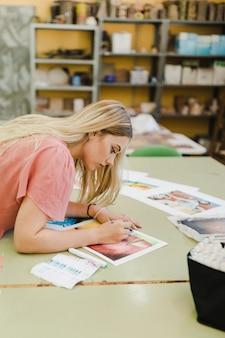 Blonde jeune femme peignant avec un crayon de couleur sur du papier au-dessus de la table
