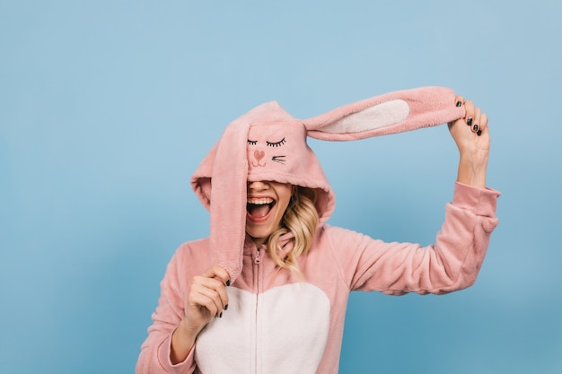 Blonde jeune femme posant en costume de lapin rose