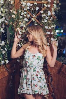 Blonde jeune femme posant devant une décoration florale