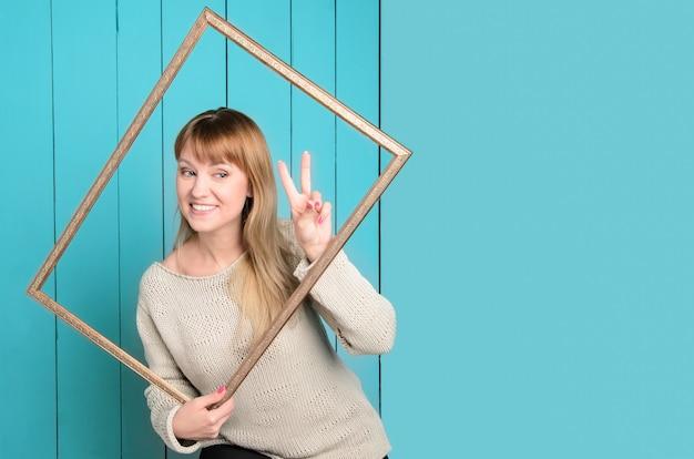 Blonde jeune femme en pull tricoté avec des cheveux lâches détient un cadre photo en bois vintage montrant le signe v du doigt et les sourires.