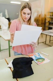 Blonde jeune femme regardant toile papier debout derrière la table