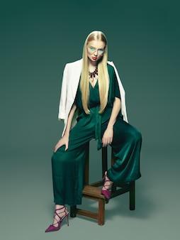 Blonde jeune femme en robe verte élégante.