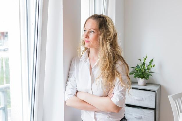 Blonde jeune femme s'appuyant sur le mur en regardant la fenêtre