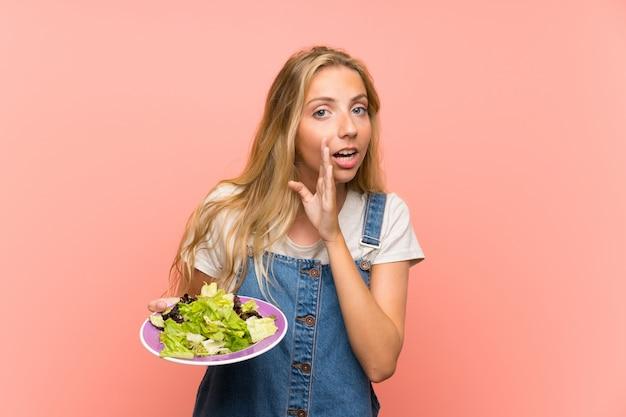Blonde jeune femme avec une salade sur un mur rose isolé murmurant quelque chose