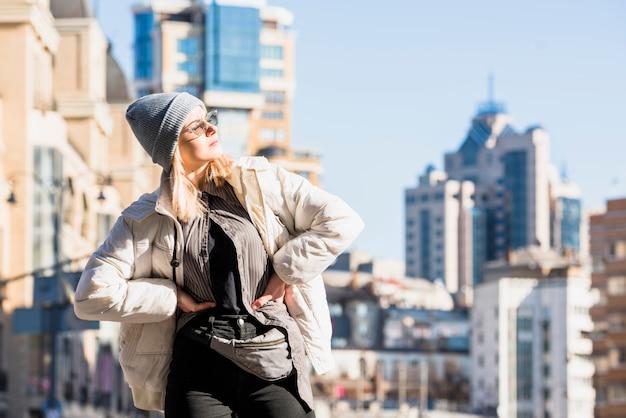 Blonde jeune femme avec ses mains sur les hanches debout devant les toits de la ville posant