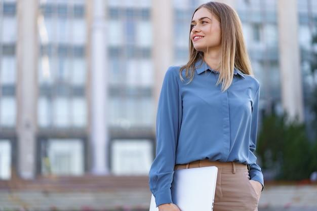Blonde jeune femme souriante portrait portant une chemise douce bleue sur le bâtiment