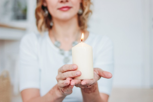 Blonde jeune femme en vêtements blancs avec mehendi tenant une bougie allumée
