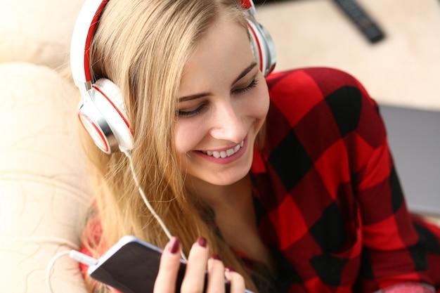 Blonde jeune jolie femme écouter de la musique casque rêve relax concept