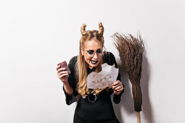 Blonde jeune sorcière à lunettes lecture sort. portrait intérieur de l'assistant maléfique évoque à halloween.