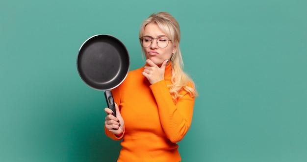Blonde jolie femme apprentissage cuisinier avec une casserole