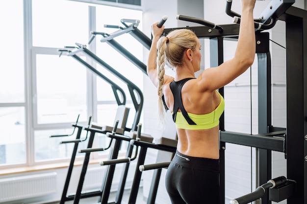 Blonde jolie femme mince portant un soutien-gorge de sport fait des exercices de traction sur la barre horizontale dans un centre de remise en forme ou une salle de sport.