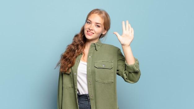 Blonde jolie femme souriante et à la recherche amicale, montrant le numéro cinq ou cinquième avec la main en avant, compte à rebours