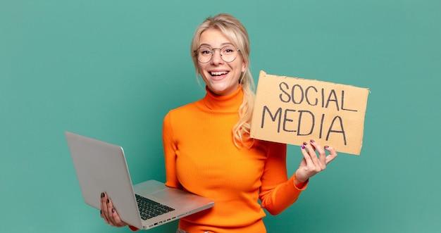 Blonde jolie femme tenant un ordinateur portable et un signe de médias sociaux