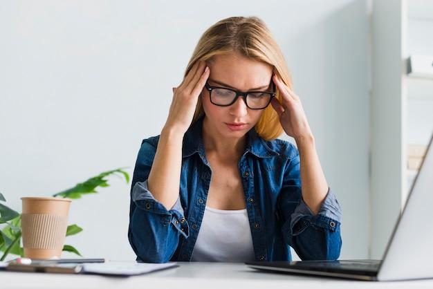 Blonde à lunettes touchant la tempe au bureau