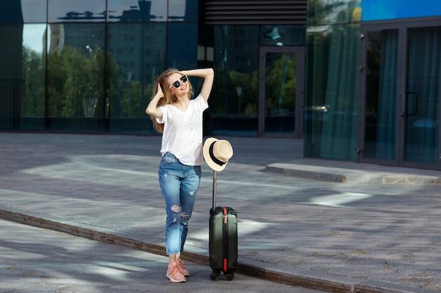 Blonde à lunettes avec une valise à roulettes en été au soleil voyage et vacances