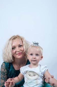 Blonde maman et sa fille en studio sur une surface blanche