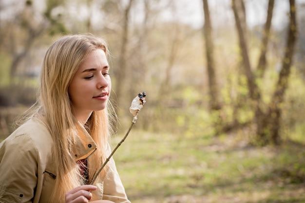 Blonde manger des guimauves sur un bâton