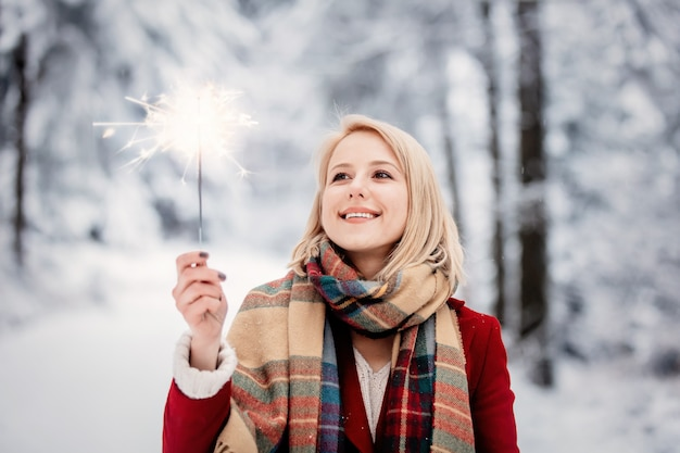 Blonde en manteau rouge avec cierge magique dans une forêt enneigée
