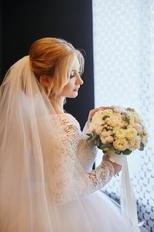 Blonde mariée en robe de mariée blanche