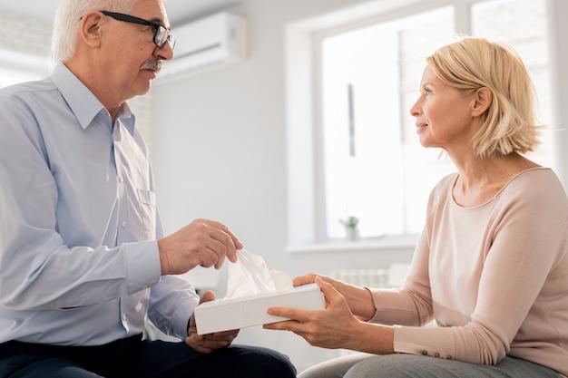 Blonde mature woman holding fort avec des mouchoirs en papier tout en offrant un à senior man pendant la session
