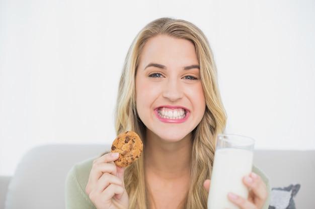 Blonde mignonne heureuse manger des biscuits avec du lait assis sur un canapé confortable