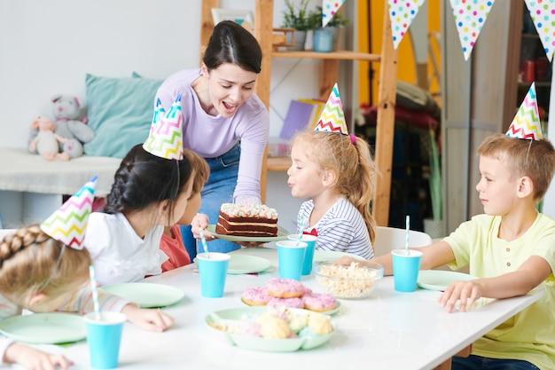 Blonde mignonne petite fille soufflant des bougies sur le gâteau d'anniversaire par table servie entre ses amis et sa mère lors de la célébration à la maison