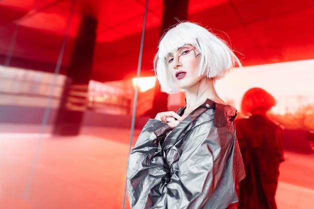Blonde de mode dans une image futuriste sur un rouge.