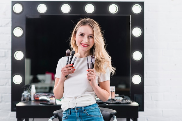 Blonde montrant des pinceaux pour le maquillage en salon