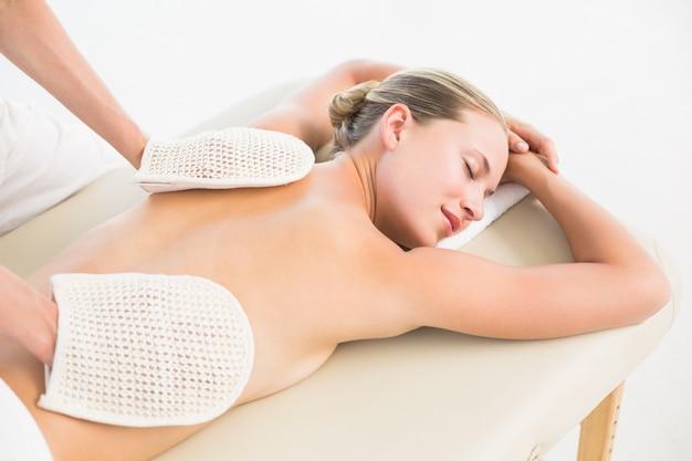 Blonde paisible bénéficiant d'un massage du dos exfoliant