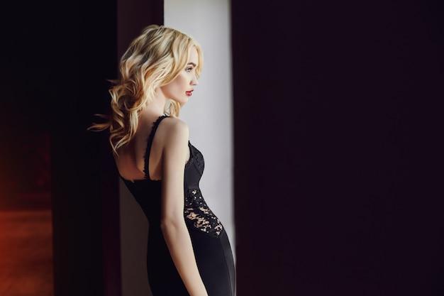 Blonde parfaite en robe noire photo d'art de mode