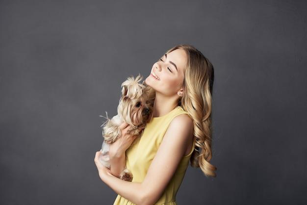 Blonde avec un petit chien maquillage posant fond isolé