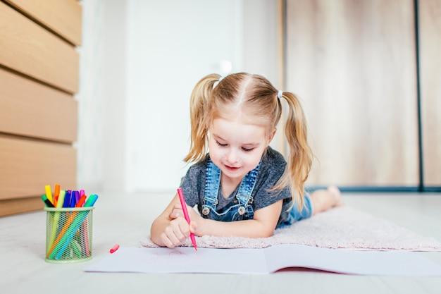 Blonde petite fille heureuse avec deux ponytales dessin et écriture allongé sur le sol à la maison. éducation préscolaire, apprentissage précoce