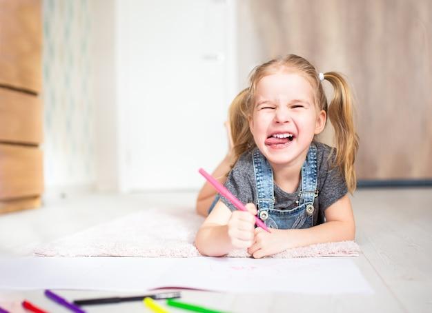 Blonde petite fille heureuse avec deux ponytales dessin et écriture allongé sur le sol à la maison et montrant sa langue. éducation préscolaire, apprentissage précoce