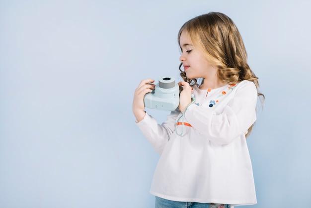 Blonde petite fille en regardant mini caméra instantanée, tenant dans les mains sur fond bleu