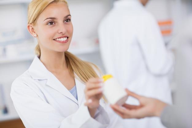 Blonde pharmacien donnant une boîte de médicaments