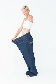 Blonde portant un pantalon trop grand avec le pouce vers le haut