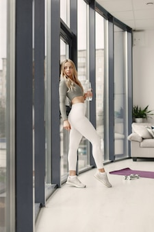Blonde posant. dame dans un costume de sport. femme à la maison près de la fenêtre.